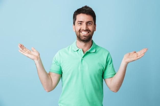Foto eines glücklichen jungen gutaussehenden bärtigen mannes, der isoliert über der blauen wand posiert, die exemplar zeigt.