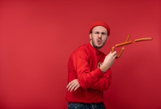 Foto eines glücklichen mannes mit bart in brille und roter kleidung. spielt würstchen wie nunchakus ninja, auf rotem hintergrund isoliert.