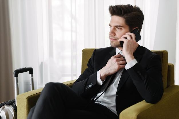 Foto eines grübelnden brünetten geschäftsmannes im schwarzen anzug, der auf dem handy spricht, während er auf einem sessel in der hotelwohnung sitzt