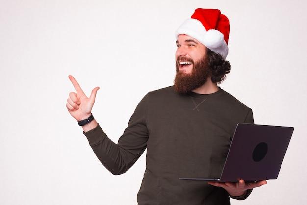Foto eines gutaussehenden bärtigen mannes mit weihnachtsmann-hut, der laptop hält und auf die ecke zeigt