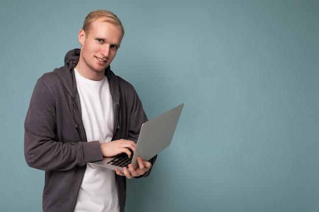 Foto eines gutaussehenden blonden mannes, der einen computer-laptop mit blick in die kamera hält, der über blauem wandhintergrund isoliert ist und ein weißes t-shirt und einen grauen pullover trägt.