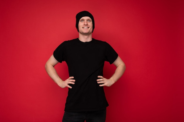 Foto eines gutaussehenden, glücklich lächelnden jungen mannes, der isoliert über einer roten hintergrundwand steht und ein schwarzes t-shirt für mockup und schwarzen hut trägt und in die kamera schaut.