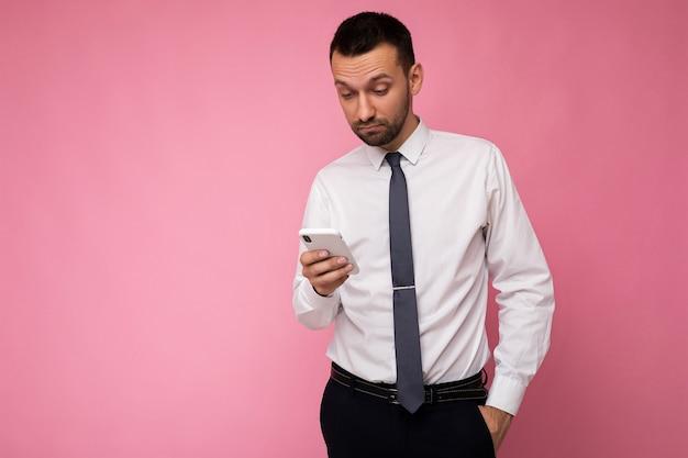 Foto eines gutaussehenden, gut aussehenden mannes, der ein lässiges weißes hemd und eine krawatte trägt, die auf rosafarbenem hintergrund isoliert sind, mit leerem raum in der hand und mit handy-messaging-sms mit blick auf den gadjet-bildschirm