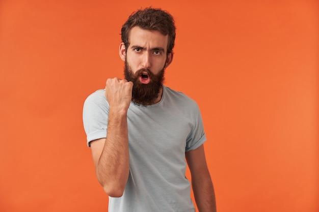 Foto eines gutaussehenden jungen mannes mit arm in faust emotion gewinnen highscore-spieler-gewinner posiert, stehend