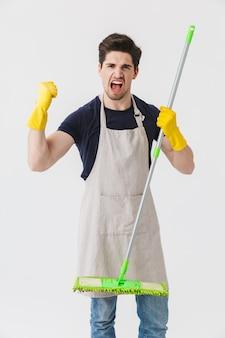 Foto eines gutaussehenden jungen mannes mit gelben gummihandschuhen zum schutz der hände, der mopp hält, während er das haus isoliert über weiß putzt