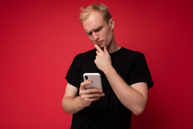 Foto eines gutaussehenden, nachdenklichen jungen blonden mannes, der über einer roten hintergrundwand isoliert ist und ein schwarzes t-shirt trägt und ein mobiltelefon verwendet, das etwas über das smartphone beobachtet, das auf den gerätebildschirm schaut und