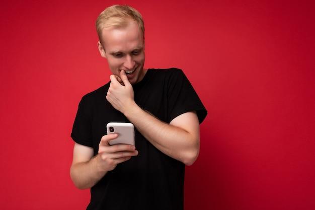 Foto eines gutaussehenden, positiven jungen blonden mannes, der über einer roten hintergrundwand isoliert ist und ein schwarzes t-shirt trägt, das ein mobiltelefon hält und verwendet und etwas über das smartphone beobachtet, das auf den gerätebildschirm schaut.