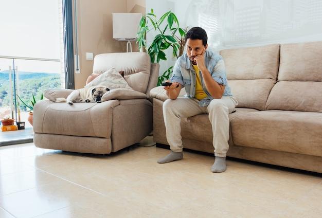 Foto eines hübschen hispanischen mannes, der auf einem sofa sitzt und fernsieht