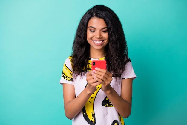 Foto eines hübschen jungen mädchens, das ein telefon mit einem strahlenden lächeln hält, das ein t-shirt mit bananendruck trägt, isoliert auf türkisfarbenem hintergrund
