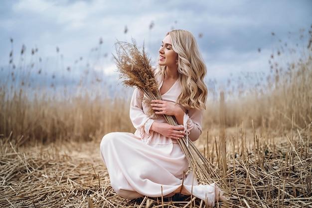 Foto eines hübschen lächelnden mädchens mit langen blonden lockigen haaren in hellen langen drees, die in einem schilffeld sitzen