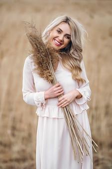 Foto eines hübschen lächelnden mädchens mit langen blonden lockigen haaren in hellen langen drees, die in einem schilffeld stehen
