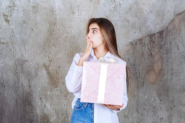 Foto eines hübschen mädchenmodells mit großem geschenk, das den mund mit der hand bedeckt