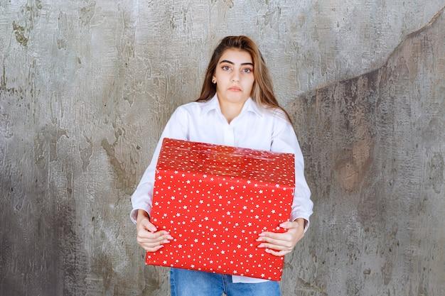 Foto eines hübschen mädchenmodells mit langen haaren, das ein großes rotes geschenk hält