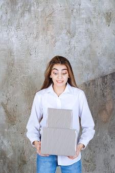 Foto eines hübschen mädchenmodells mit langen haaren, das geschenkkartons hält