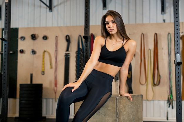 Foto eines jungen athleten in der schwarzen kleidung, der auf einer holzkiste im fitnessstudio nach dem ausführen von übungen sitzt