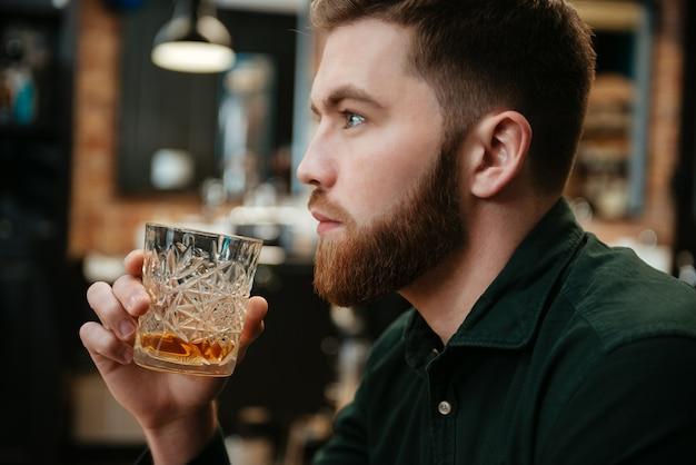 Foto eines jungen mannes, der im sessel sitzt und whisky trinkt