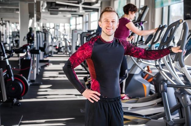 Foto eines jungen mannes - fitnesstrainer, der lächelt und die kamera auf dem hintergrund des fitnessstudios anschaut