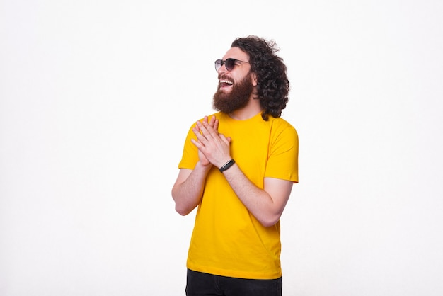 Foto eines jungen mannes mit bart, der ein gelbes t-shirt trägt und lacht