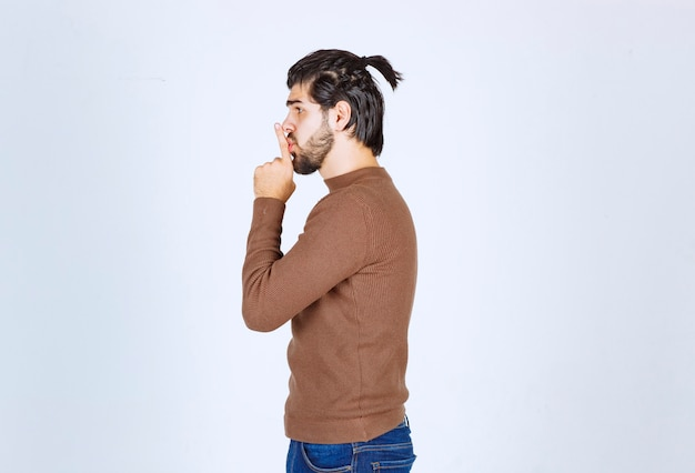 Foto eines jungen mannes mit bart, der eine stille zeigt. foto in hoher qualität