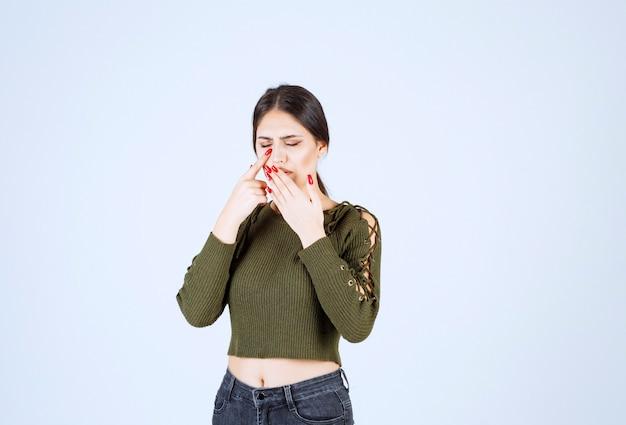 Foto eines jungen netten frauenmodells, das ihren mund vom husten bedeckt.