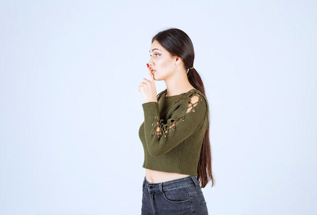Foto eines jungen reizenden frauenmodells, das stilles zeichen steht und tut.