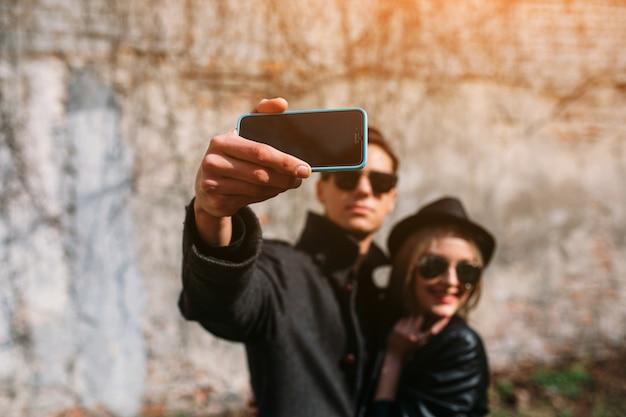 Foto eines jungen schönen paares, das selfie auf grauer wand macht