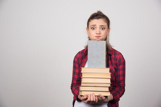Foto eines jungen studenten, der einen stapel bücher hält.