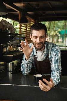 Foto eines kaukasischen barista-typs, der eine schürze trägt und lächelt, während er das smartphone im café oder kaffeehaus im freien benutzt