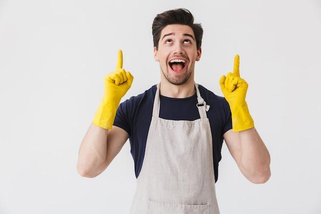 Foto eines kaukasischen jungen mannes, der gelbe gummihandschuhe zum schutz der hände trägt und mit den fingern auf den kopierraum zeigt, während er das haus isoliert über weiß putzt