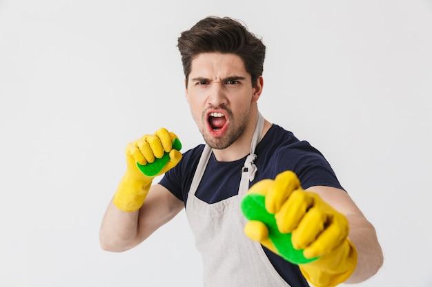 Foto eines kaukasischen jungen mannes, der gelbe gummihandschuhe zum schutz der hände trägt und schwämme hält, während er das haus isoliert über weiß putzt