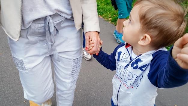 Foto eines kleinen kleinkindjungen, der seine mutter und seinen älteren bruder mit der hand hält und im herbstpark spazieren geht