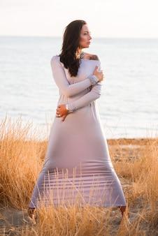 Foto eines langen kleides der schönen jungen eleganten frau in mode auf dem strand