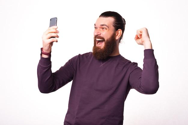 Foto eines mannes, der ein telefon hält, das es betrachtet und sehr aufgeregt ist