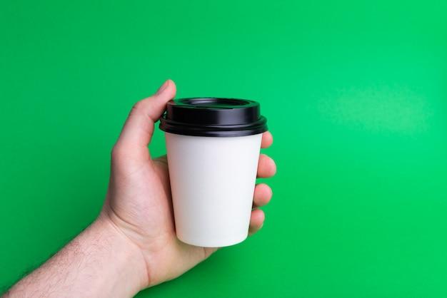 Foto eines mannes hände, die eine weiße tasse zum mitnehmen auf grün halten