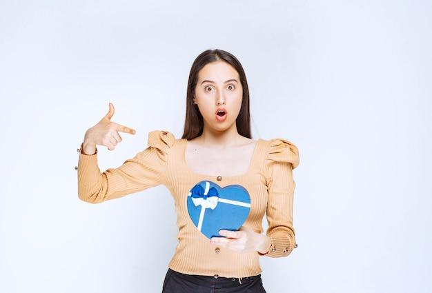 Foto eines modells der jungen frau, das auf eine herzförmige geschenkbox gegen weiße wand zeigt.