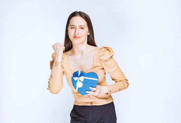 Foto eines modells der jungen frau, das eine herzförmige geschenkbox gegen weiße wand hält.