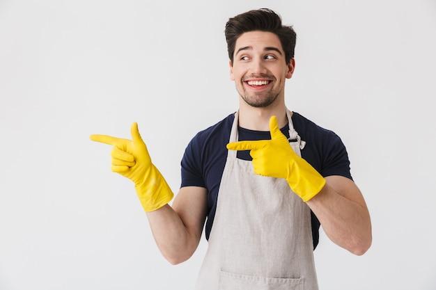 Foto eines optimistischen jungen mannes, der gelbe gummihandschuhe zum schutz der hände trägt und mit den fingern auf den kopierraum zeigt, während er das haus isoliert über weiß putzt