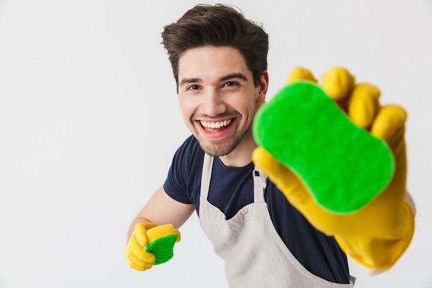 Foto eines optimistischen jungen mannes mit gelben gummihandschuhen zum schutz der hände, der schwämme hält, während er das haus isoliert über weiß putzt