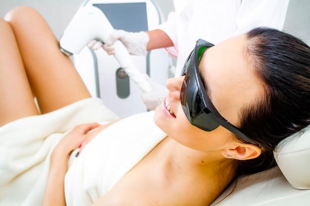 Foto eines patienten in einer kosmetikklinik über das verfahren zum entfernen unerwünschter beinhaare mit einem lasergerät.