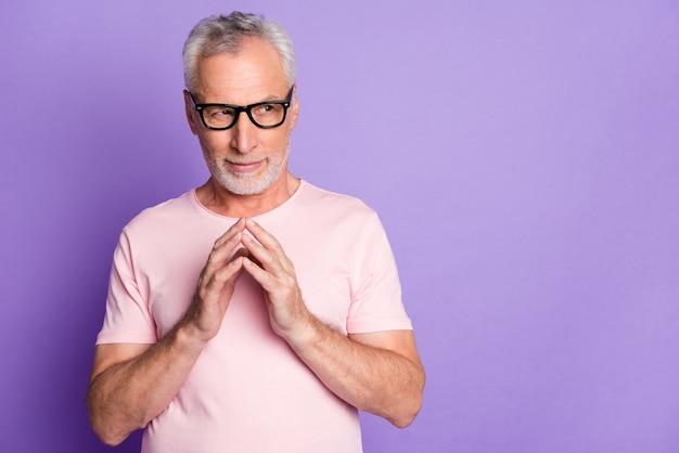 Foto eines pensionierten alten mannes, der arme hält, sieht seitlich leer aus und trägt eine brille rosa t-shirt isoliert lila farbhintergrund
