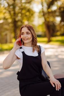 Foto eines positiven fröhlichen teenager-mädchens verbringt zeit im park und mit handy.