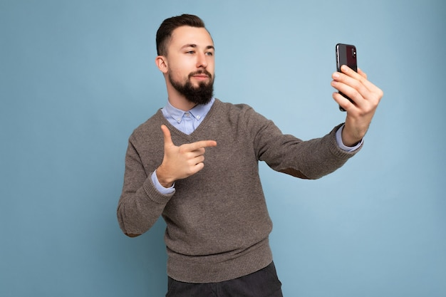 Foto eines positiven, gutaussehenden jungen, unrasierten, brünetten mannes mit bart, der einen lässigen grauen pullover trägt und