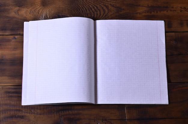 Foto eines sauberen weißen schulscheckhefts auf einem braunen hölzernen hintergrund. idee oder nachrichtenkonzept.