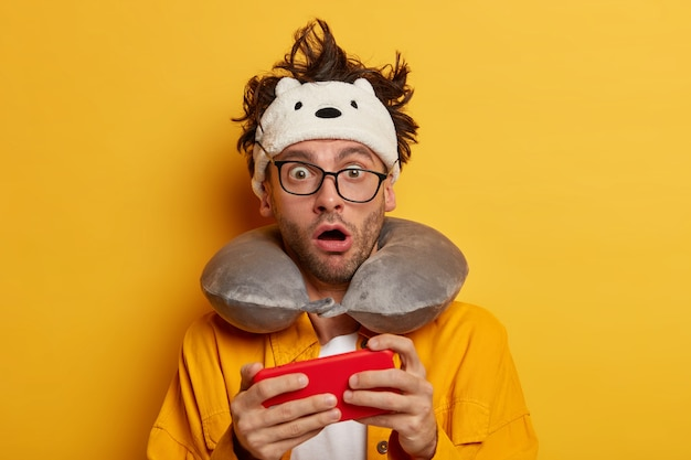Foto eines schockierten verlegenen mannes, der von modernen technologien abhängig ist, spielt videospiele auf smartphone-gerät, während im flugzeug reist