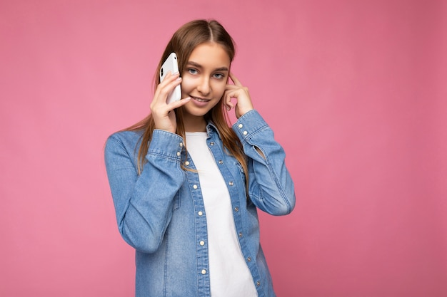 Foto eines schönen lächelnden, glücklichen jungen blonden weiblichen pesons, der ein lässiges blaues jeanshemd trägt, isoliert über rosafarbenem hintergrund, das in der hand hält und auf dem handy mit blick auf die kamera spricht.