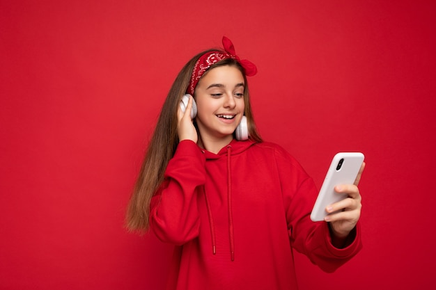 Foto eines schönen, positiv lächelnden brünetten mädchens, das einen roten hoodie auf rotem hintergrund trägt