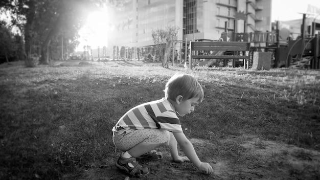 Foto eines süßen kleinen kleinkindjungen, der im park sitzt und sand gräbt