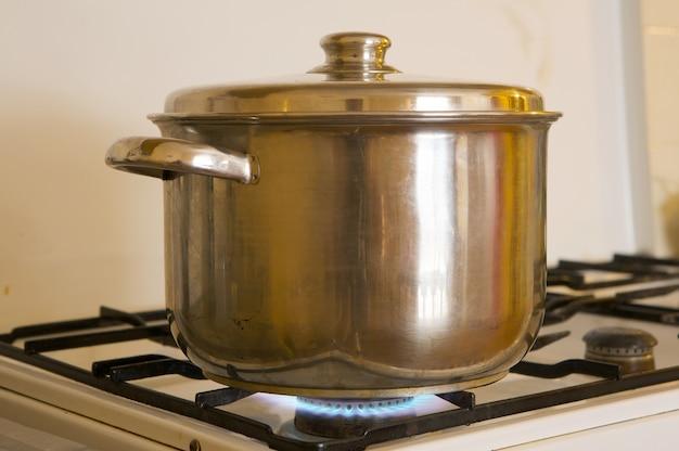 Foto eines topfes auf den flammen des brennenden gases des küchenofens