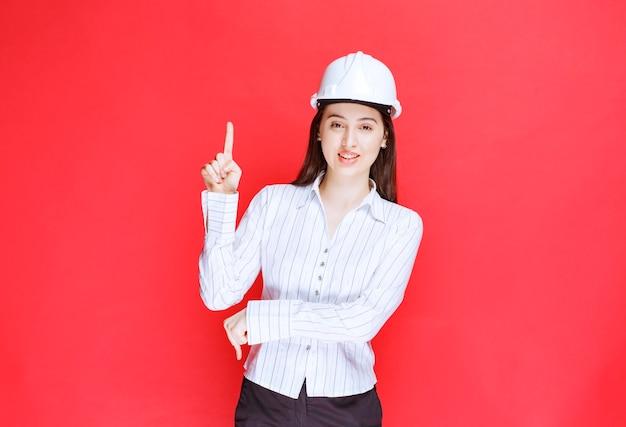 Foto eines tragenden sicherheitshutes der schönen geschäftsfrau, der oben zeigt.