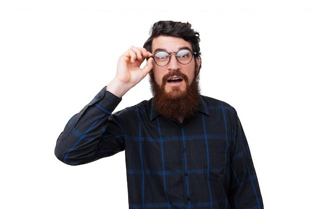 Foto eines überraschten bärtigen mannes, der seine brille berührt